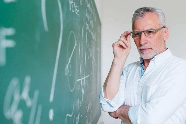 Concentrated aged math teacher looking at chalkboard Free Photo