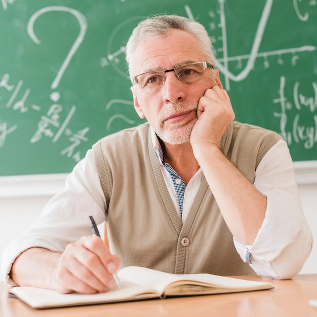 Concentrated aged math teacher thinking at desk Free Photo