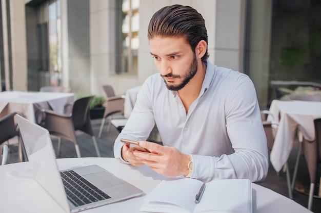 集中して落ち着いた若い男がテーブルに座ってノートパソコンの画面を見ています。彼は電話を手に持っています。テーブルの上にペンで開いたノートがあります。彼は働く。 Premium写真
