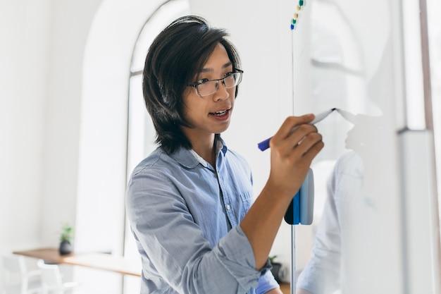 Uomo asiatico concentrato in camicia blu con lavagna a fogli mobili e pennarello per lavoro Foto Gratuite