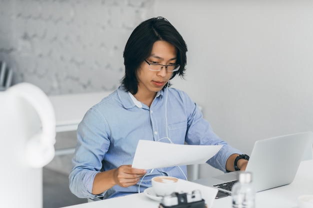 Concentrated asian office worker in earphones reading documents at workplace. indoor portrait of chinese freelance it-specialist drinks coffee while using with laptop. Free Photo
