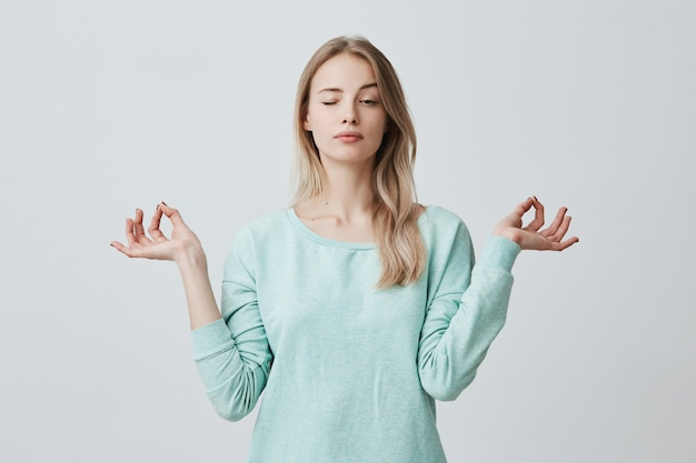 Concentrated attractive female with long dyed hair dressen in blue stands in lotus pose, meditates and enjoys peaceful atmosphere, closes eyes, tries to relax after hard working day. mudra gesture Free Photo