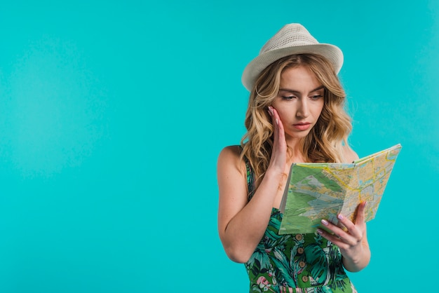 Concentrated attractive young woman in hat and dress looking at map Free Photo