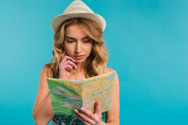 Concentrated attractive young woman in hat looking at map Free Photo