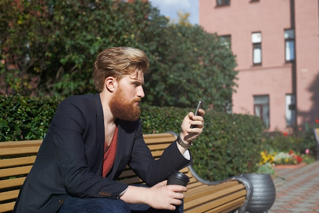 Concentrated bearded hipster using smarphone while sits on a bench Free Photo