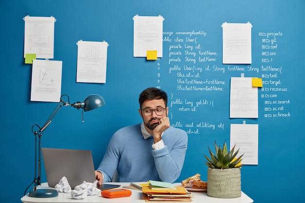 Сосредоточенный бородатый веб-разработчик улучшает новую версию сайта, сидит за белым столом, загруженный блокнотами, закуской, чашкой чая и горшечным растением, печально смотрит на проблему проекта, наклоняется к руке Бесплатные Фотографии
