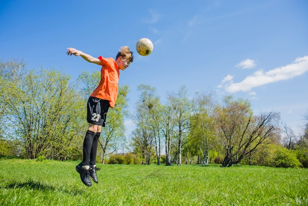Concentrated boy hitting the ball with his head Free Photo
