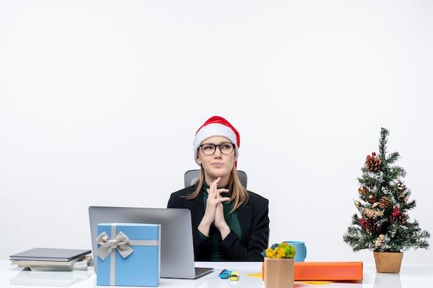Donna d'affari concentrato con cappello di babbo natale seduto a un tavolo con un albero di natale e un regalo su di esso in ufficio su sfondo bianco Foto Gratuite