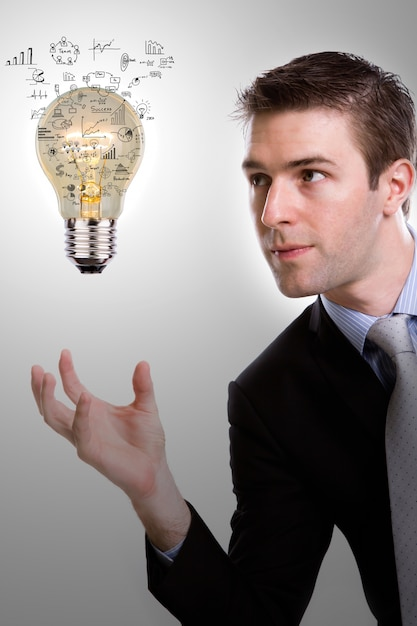 Concentrated businessman looking at a light bulb with diagrams Free Photo