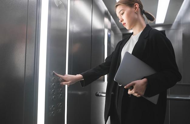 그녀의 손에 노트북을 들고 엘리베이터의 버튼을 누르면 집중된 사업가. 프리미엄 사진