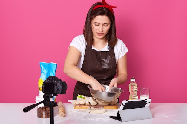 Concentrated busy talented housewife holding bowl with whisk in one hand Premium Photo