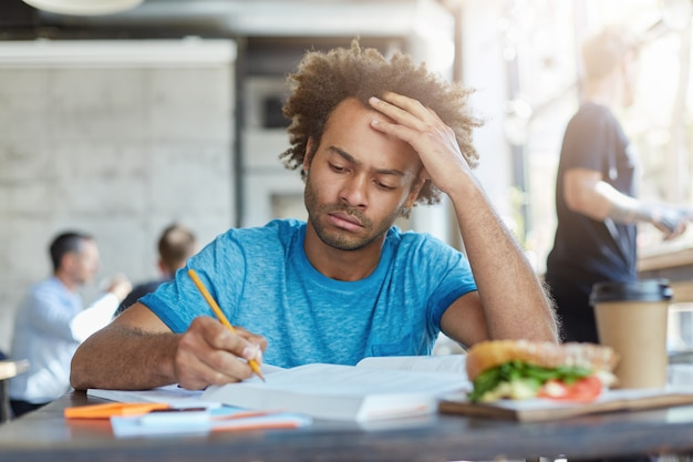 Concentrated casually dressed dark-skinned unshaven student studying at coffee shop, writing down in exercise book, making research or preparing for examination at college, having serious look Free Photo