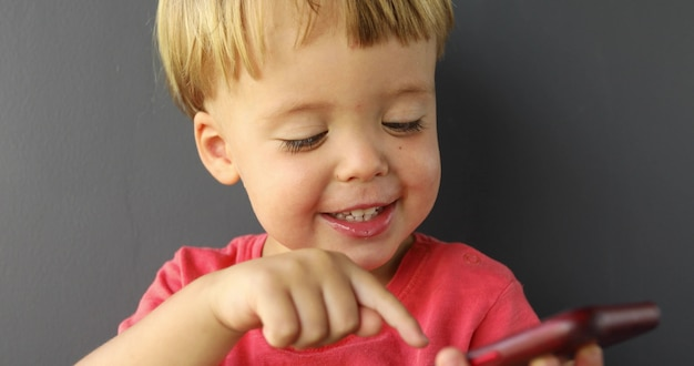 Concentrated child tapping cell phone screen Premium Photo