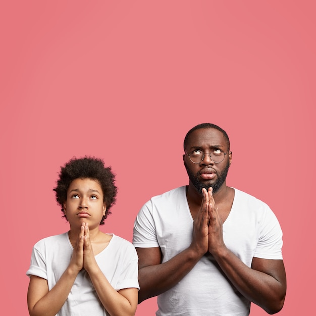 Concentrated dad and son pose together against pink studio wall, keep hands in praying gesture, believe in something good Free Photo