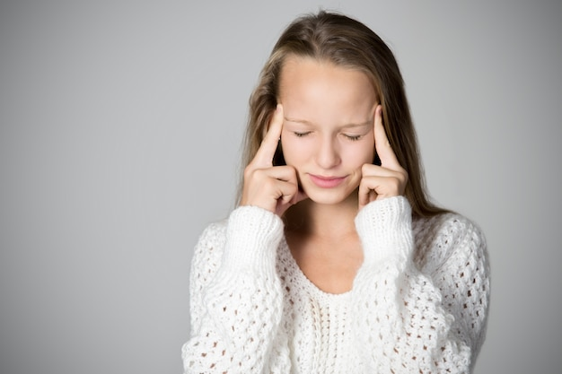 Concentrated girl with fingers on the forehead Free Photo