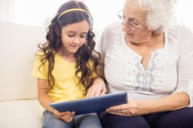 Concentrated granddaughter using tablet with grandmother at home Premium Photo