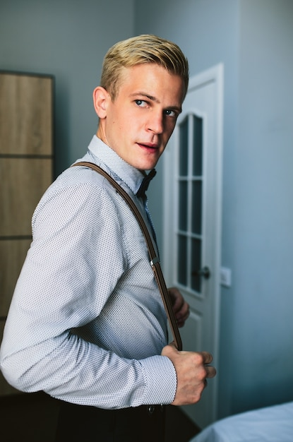 Concentrated groom holding his suspenders Free Photo