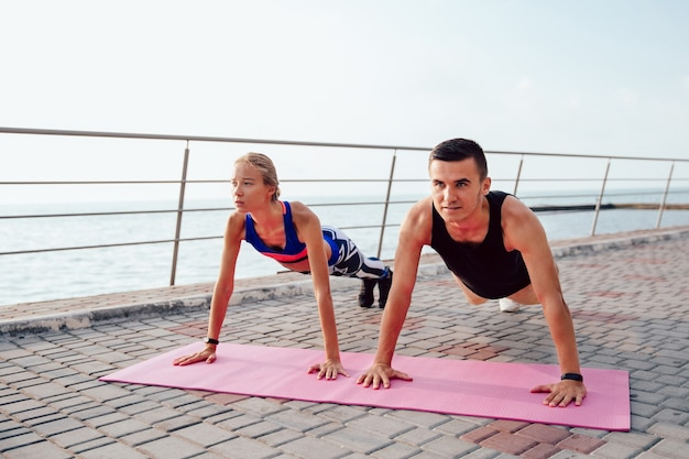 Concentrated handsome man and lovely girl doing push ups while training outdoors Free Photo