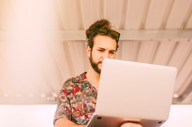 Concentrated hipster working on laptop outdoors Free Photo