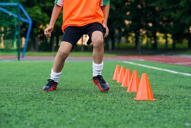 Сосредоточенный юный футболист, бегущий среди конусов Premium Фотографии