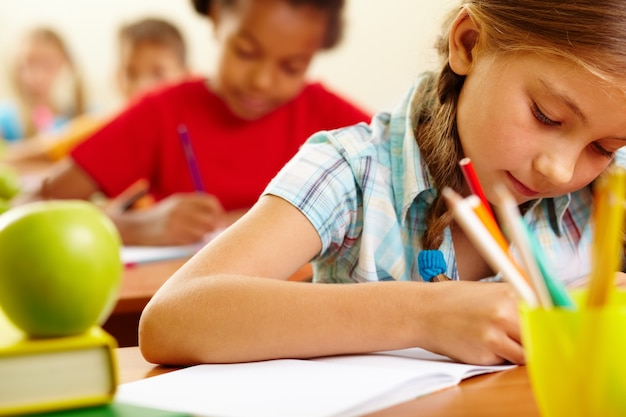 Concentrated little girl doing homework Free Photo