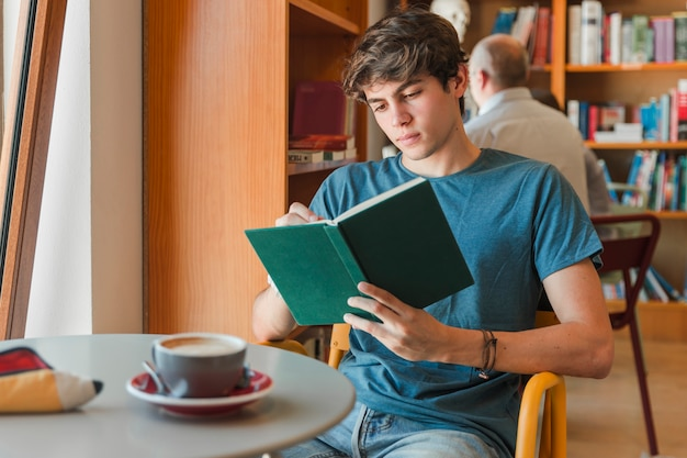 Concentrated man enjoying reading book   Free Photo
