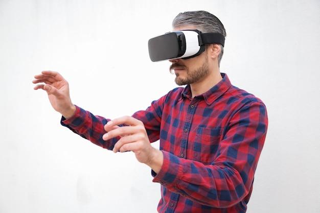 空気に触れるvrヘッドセットで集中している男 無料写真