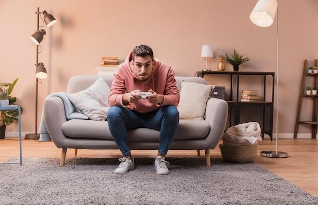 ソファで遊ぶことに集中している男 無料写真