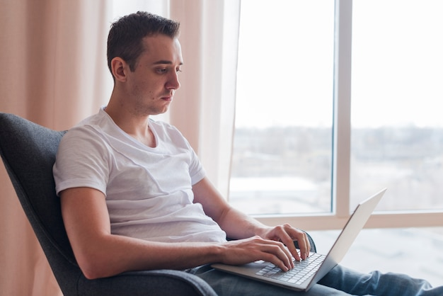Concentrated man sitting on chaor and typing on laptop near window Free Photo