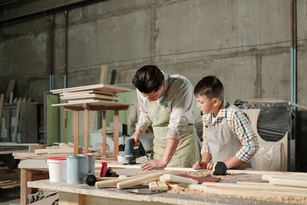 ワークショップで息子に板を挽く方法を見せながら、研磨機を使ってエプロンに集中した中年の大工 Premium写真