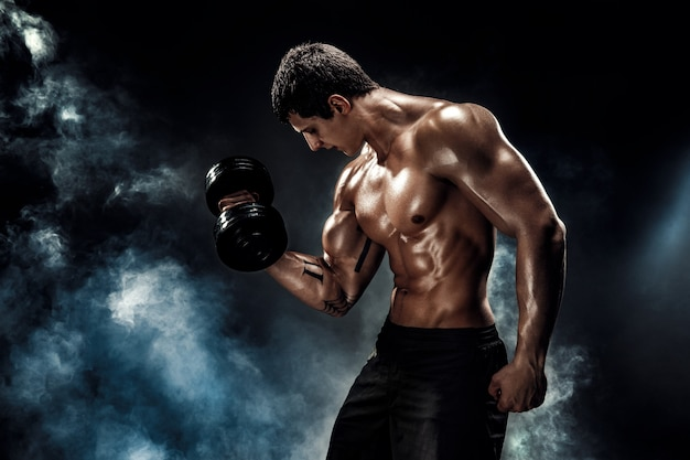 Concentrated muscular man doing exercise with dumbbell Premium Photo