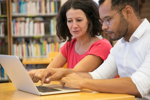 Concentrated people studying with laptop together Free Photo