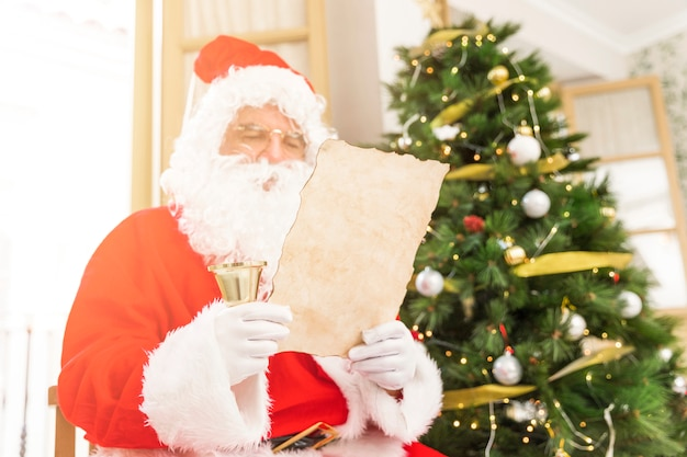 Concentrated santa claus reading letter Free Photo