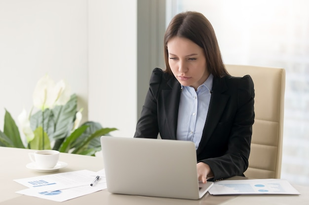 Concentrated serious businesswoman making report, working with laptop in office Free Photo