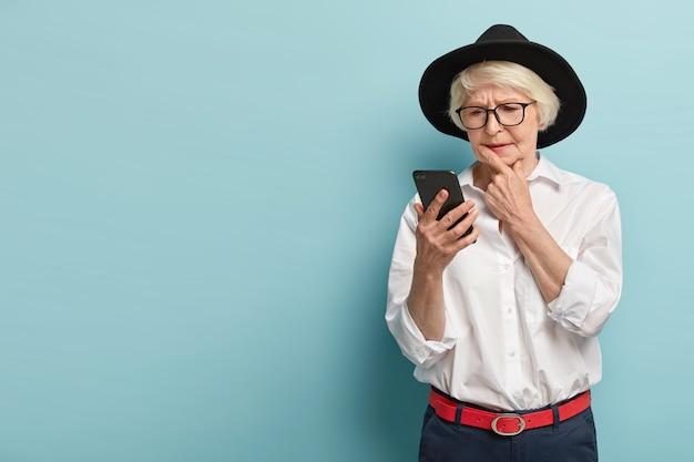 集中した真面目なおばあちゃんは、ファッショナブルなヘッドギア、服を着て、スマートフォンに焦点を当て、オンラインでニュースを注意深く読み、空きスペースのある青い壁の上のモデル、電子メールボックスをチェックします。現代の年金受給者 無料写真