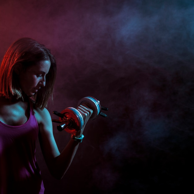 Concentrated sportive woman with dumbbell Free Photo