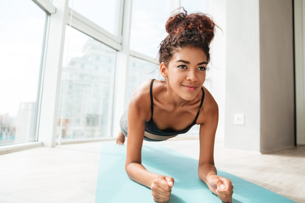 Concentrated sportswoman standing in plank position Free Photo