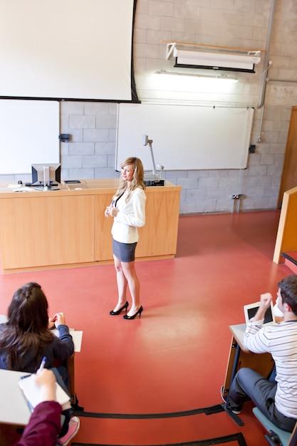 Концентрированные ученики слушают своего учителя в университете Premium Фотографии