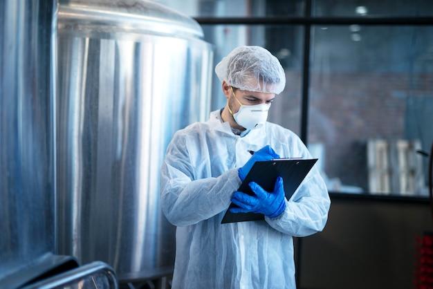 食品工場での生産を制御する白いスーツの集中技術者の専門家 無料写真