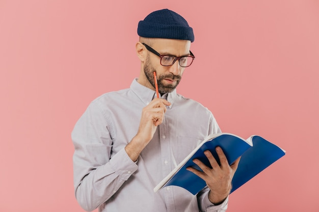 Concentrated unshaven adult man holds blue textbook and pencil, reads necessary information Premium Photo