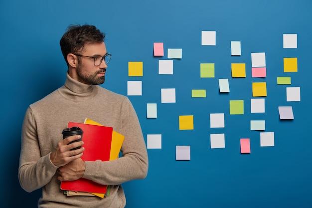 Il ragazzo con la barba lunga concentrato prende il caffè, si volta sul muro blu con note colorate adesive, ha molto lavoro e compiti Foto Gratuite