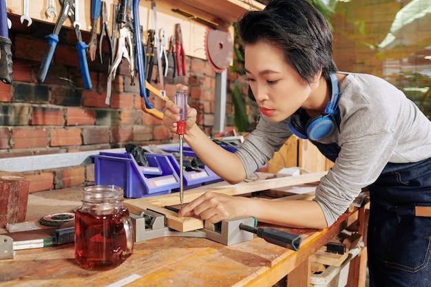 Сосредоточенная вьетнамская плотница с помощью отвертки и тисков соединяет деревянные доски Premium Фотографии