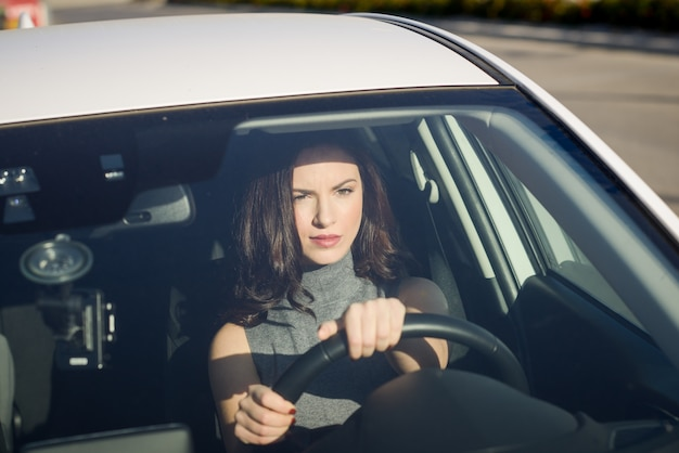 Concentrated woman driving her car Free Photo