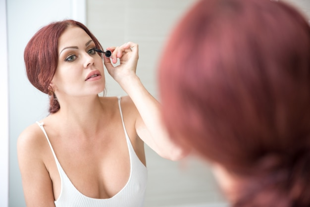Concentrated woman putting on makeup at mirror Free Photo