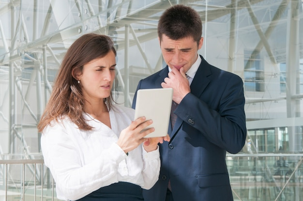Concentrated woman showing man data on tablet, thinking hard Free Photo
