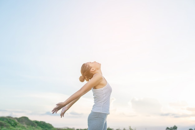 Concentrated woman stretching her arms with sky background Free Photo