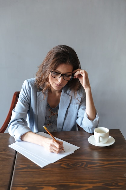 Concentrated woman writing notes indoors near cup of coffee Free Photo