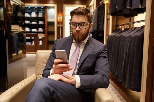 Концентрированный молодой бородатый бизнесмен, сидя в помещении в чате Бесплатные Фотографии