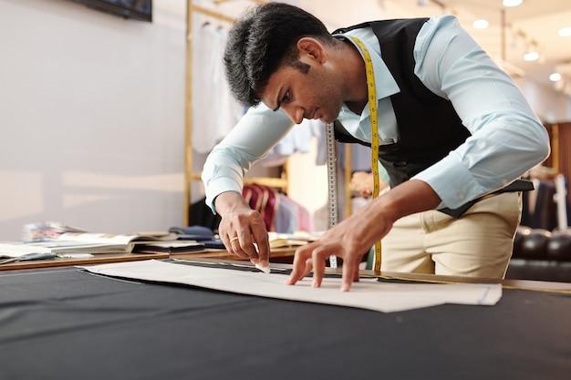 블랙 패브릭에 젊은 인도 재단사 추적 바느질 패턴을 집중 프리미엄 사진