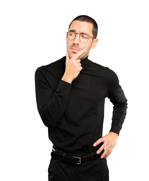 Сосредоточенный молодой человек делает жест недоверия Premium Фотографии